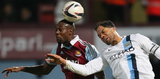 West Ham striker Carlton Cole (left) heads the ball under pressure from Man City defender Joleon Lescott as City cruise into the League Cup final. Photo / AP