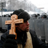 An Orthodox priest prays in front police officers as they block a street after clashes in central Kiev, Ukraine. Photo / AP
