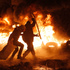 Protesters throw tyres onto a fire during clashes with police in central Kiev, Ukraine. Photo / AP