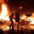 Protesters throw tires into a fire as they clash with police in central Kiev, Ukraine. Photo / AP