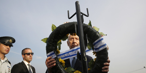 Israel's President Shimon Peres lays a wreath during the funeral of former Israeli Prime Minister Ariel Sharon. Photo / Getty Images