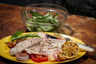 Grilled fish with tomatoes, potatoes and lemon. Photo / Michael Craig