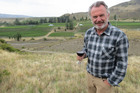Two Paddocks founder and actor Sam Neill toasts his winery's new acquisition of a fourth vineyard in Central Otago, the 6ha Desert Heart in Bannockburn, seen behind him. Photo / James Beech