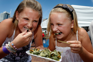 Gracie Bush (left), and Felicity Rood, taste some sea escargot at the Auckland Seafood Festival. Photo / Sarah Ivey