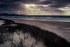 Light rays filter through the clouds at dusk along Mason Bay, Stewart Island. Photo / Hawkes Bay Today