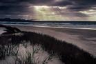 Light rays filter through the clouds at dusk along Mason Bay, Stewart Island. Photo / Hawkes Bay Today
