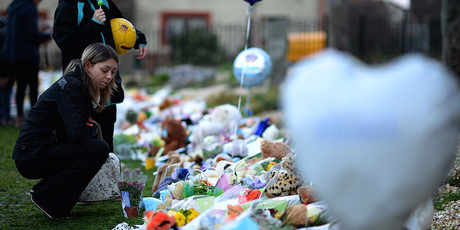 Members of the public lay flowers and candles near to the house in Ferry Gait Crescent where three year old Mikaeel Kular was reported missing. Photo / Getty Images