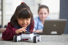 Yule Chon, 8, and Ashley McChesney, 11, of Marina View School in Auckland, work with a robot as part of learning computer programming. Photo / Chris Loufte