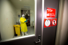 Clinical head of infectious diseases at Middlemore Hospital, Dr Stephen McBride, gets kitted out in safety gear at the hospital's infections wing. Photo / NZ Herald