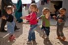 Syrian Kurdish refugee children from the Kobani area play at a refugee camp near the Turkey-Syria border. Photo / AP