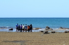 Family members hold a karakia before police divers discovered Ed Adams' body. Photo / Duncan Brown