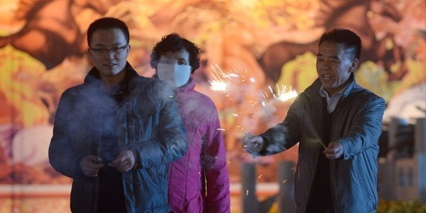 A Chinese family lights fireworks at a square in Lanzhou, northwest China's Gansu province on the eve of the Lunar New Year. Photo / AFP