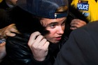 Canadian musician Justin Bieber is swarmed by media and police officers as he turns himself in to city police for an expected assault charge in Toronto. Photo/AP