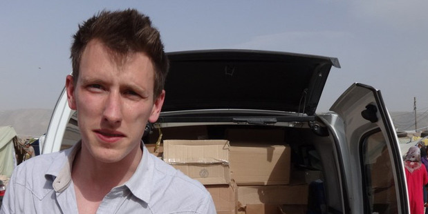 Peter Kassig standing in front of a truck filled with supplies for Syrian refugees. Photo / AP