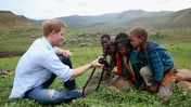 Britain's Prince Harry shows children a photograph he has taken during a visit to a herd boy night school constructed by his charity Sentebale in Mokhotlong.