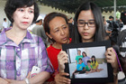 Relatives hold a picture of the Herumanto Tanus family as they wait for news from the missing AirAsia plane at Juanda Airport, in Surabaya.
