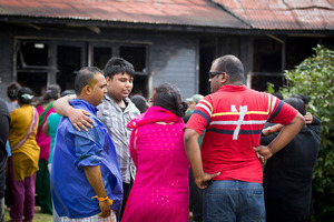 Family mourn after a fire gutted their home in Mangere East today. Photo / Sarah Ivey