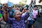 A Thai woman holds her ID card and joins with others to demand to vote outside the closed down Dindaeng district office in Bangkok on Sunday. Photo / AP