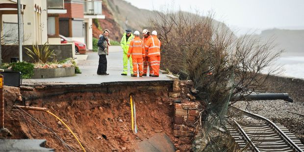 Workmen assess a huge hole exposing ground services and exposed railway track after the sea wall collapsed in Dawlish, England. Photo / AP