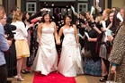 Rachel Briscoe (left) and Jess Ivess are showered in petals after their same-sex wedding ceremony.  Photo / Alan Gibson