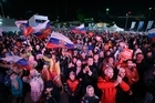 Supporters wave the Russian national flag and scream