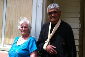 Frank and Barbara Watene standing outside bordered up windows at their Naenae home. Photo / Rebecca Quilliam