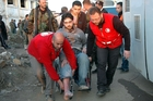 Syrian Arab Red Crescent members (in red uniforms) help evacuate an injured man from the battleground city of Homs to a rescue bus. Photo / AP