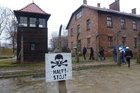 A warning sign at Auschwitz as visitors pass by on a guided tour. Photo / Jared Savage