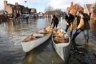 Boats are loaded with sandbags on a flooded street in Datchet. Photo / AP