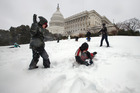 Children play in the snow on Capitol Hill, as winter weather shut down Washington. Photo / AP