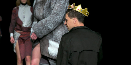 A streaker in a G-string, crown and overcoat kneels before a model on the runway. Photo / AP