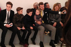 David Beckham takes a photo of his four children in the front row before the Victoria Beckham show, as daughter Harper sits in Beckham's lap. Photo / AP
