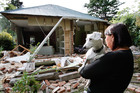 A woman and her dog survey her quake-hit home in Christchurch. File photo / Brett Phibbs