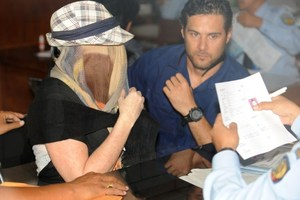 Schapelle Corby, her face covered, sits at a correction bureau in Denpasar on Indonesia's resort island of Bali. Photo / AFP