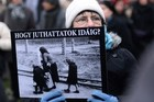 A demonstrator holds a poster of a woman with two children at a Nazi death camp with a text reading 'How were you able to go so far'. Photo / AFP