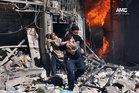 Men help survivors out of a destroyed building after a Syrian forces warplanes attacked in Aleppo, Syria. Photo / AP/Aleppo Media Center (AMC)