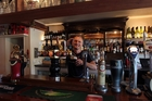 Uwe Dorr serves a pint at The British Isles Inn in Rothesay Bay. Photo / Doug Sherring