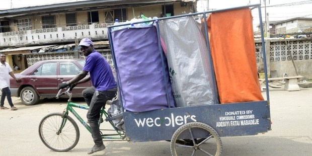Loading A Wecycler peddle through the streets with a special bicycle, picking up bags of recyclable goods from subscribers. Photo / AFP
