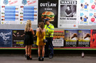 Glen Cooper writes up a ticket for young women caught with alcohol in an alcohol-free zone in Wellington. Photo / Hagen Hopkins