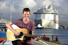 Fletcher Oxford serenades the crowd as they farewell cruise ship passengers. Photo/George Novak