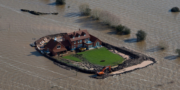 Flood waters inundate the area as one house stands alone near the flooded village of Moorland in Somerset, southwest England. Photo / AP