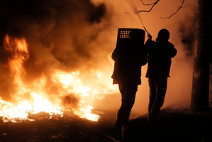 Activists extinguish a tree which caught fire at the burning barricades close to Independence Square. Photo / AP