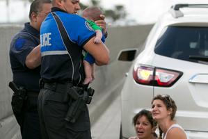 Officer Amauris Bastidas helps rescue a five-month-old baby boy, Sebastian de la Cruz. Photo / AP Photo/The Miami Herald, Al Diaz