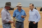 Prime Minister Tony Abbott (right), seen talking to drought-stricken farmers, has fallen in the polls but approval of his Government is up. Photo / Getty Images