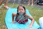 Ruby, 6, cools down on a waterslide as temperatures and humidity soared at the weekend.