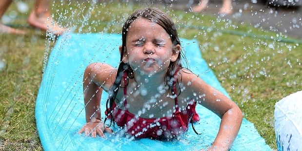 Loading Ruby, 6, cools down on a waterslide as temperatures and humidity soared at the weekend.