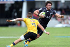 TJ Perenara of the Hurricanes looks to tackle Ryan Kankowski of the Sharks. Photo / Getty