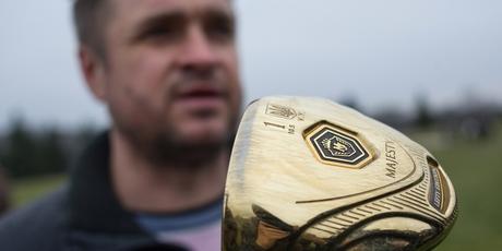 A man holds a golf club with the name of Ukrainian President Viktor Yanukovych. Photo / AP