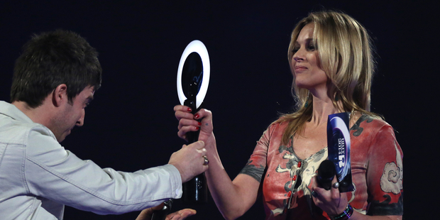 Kate Moss is seen on stage accepting the award for British Male Solo Artist on behalf of winner David Bowie from Noel Gallagher at the BRIT Awards 2014. Photo / AP