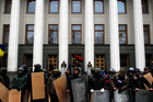 Anti-government protesters stand guard in front of Ukraine's Parliament in Kiev - they are now in control. Photo / AP